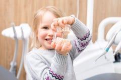 Peu fille montre le modèle artificiel de la mâchoire d'enfant dans la clinique dentaire pédiatrique photo libre de droits