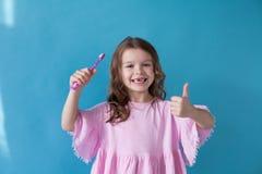 Peu fille nettoie la bosselure de brosse à dents de dents gentille photos stock