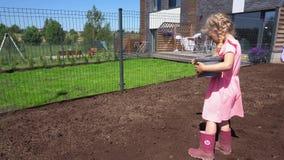 Peu fille plantant de nouvelles graines de pelouse dans le sol dans la cour de maison urbaine Mouvement de cardan banque de vidéos