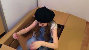 Peu fille s'asseyant dans la boîte en carton comme une voiture banque de vidéos