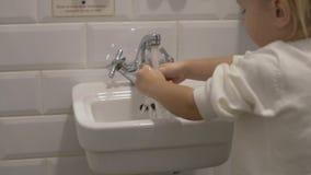 Peu fille se lave les mains dans l'évier de bébé banque de vidéos