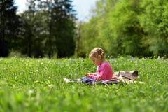 Peu fille se reposant sur un pré vert parmi des fleurs de pré images stock