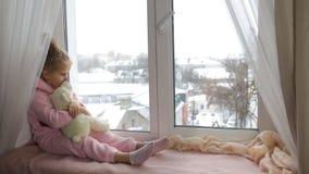 Peu fille se repose sur le rebord de fenêtre clips vidéos