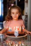 Peu fille soufflant des bougies sur un gâteau d'anniversaire sur son espace de copie d'anniversaire images libres de droits