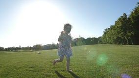 Peu fille spéciale des besoins courant sur l'herbe en parc banque de vidéos