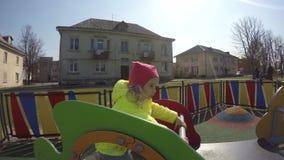 Peu fille sur l'oscillation colorée dans le terrain de jeu de parc de ville Enfant actif heureux clips vidéos