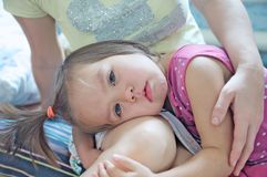 Peu fille triste sur des genoux de mères Participation de mère pleurant peu de fille apaisement vers le bas de l'enfant en bas âg image libre de droits