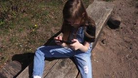 Peu fille utilisant le smartphone au parc sur le banc banque de vidéos