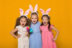 Peu filles avec des oreilles de lapin de Pâques tenant les oeufs colorés images libres de droits
