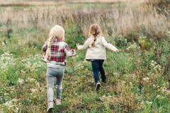 Peu filles courant par un pré Soeurs adorables ayant l'amusement sur une nature Deux petites amies Heureux et sain images libres de droits