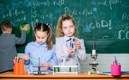 Peu filles et gar?on dans le laboratoire La science de chimie Peu badine gagner la chimie dans le laboratoire d'?cole Petits enfa images libres de droits