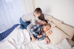 Peu fils réveille le papa de maman dans le lit et pendant le matin images stock