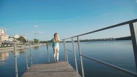 Peu fonctionnement blond sur le quai sous le ciel lumineux à l'étang clips vidéos