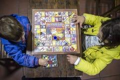 Peu frères jouant le jeu d'oie au-dessus de la table en bois de cru photo stock