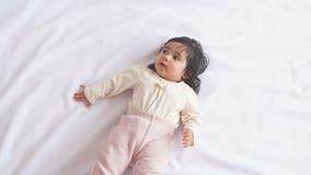 Peu fuselage porteur de bébé drôle se trouvant sur la couverture blanche banque de vidéos