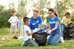 Peu garçon afro-américain rassemblant des déchets avec des volontaires photo stock