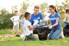 Peu garçon afro-américain rassemblant des déchets avec des volontaires image libre de droits