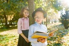 Peu garçon 6,7 années avec le chapeau, les verres, le livre de lecture et la fille 7,8 années image stock