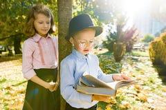 Peu garçon 6,7 années avec le chapeau, les verres, le livre de lecture et la fille 7,8 années photographie stock libre de droits
