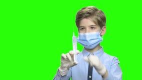 Peu garçon avec la seringue et le masque protecteur banque de vidéos