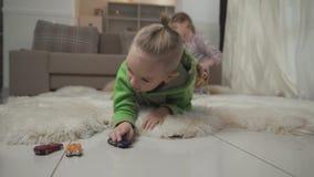 Peu garçon avec les jeux élégants de coupe de cheveux avec ses toycars se trouvant sur le plancher sur le tapis pelucheux Soeur j banque de vidéos