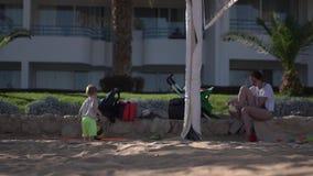 Peu garçon avec les promenades de boule près de sa mère - l'action sur la cour de volleyball banque de vidéos