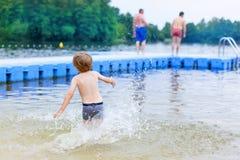 Peu garçon blond d'enfant ayant l'amusement avec l'éclaboussement dans un lac, outdoo Photos stock
