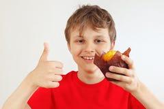 Peu garçon coupé dans une chemise rouge recommande le petit pain sur le fond blanc photographie stock libre de droits