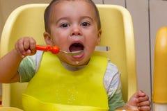 Peu garçon d'enfant apprend à manger au children& x27 ; table de s dans la cuisine Le bébé mange drôle Peu bébé mange avec une so images libres de droits