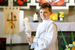 Peu gar?on d'enfant recevant sa premi?re sainte communion Bougie heureuse de bapt?me de participation d'enfant Tradition dans l'? photo stock