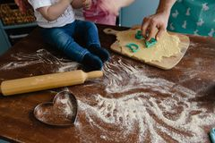 Peu garçon dans des jeans mélangeant la farine dans la cuisine sur une table faisant un certain désordre images stock