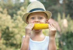 Peu garçon dans le chapeau de paille manger l'épi de maïs dans le jardin photographie stock