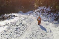 Peu garçon dans une salopette orange marchant sur la route couverte de neige dans un jour ensoleillé d'hiver conifére de forêt Vu image stock