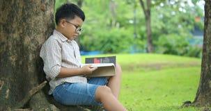 Peu garçon dedans se repose sous l'arbre un jour ensoleillé et lit un livre banque de vidéos