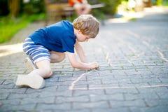 Peu garçon drôle blond d'enfant jouant le jeu de marelle sur le terrain de jeu dehors Images libres de droits