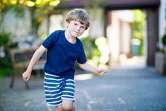Peu garçon drôle blond d'enfant jouant le jeu de marelle sur le terrain de jeu dehors Photos libres de droits