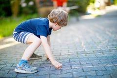 Peu garçon drôle blond d'enfant jouant le jeu de marelle sur le terrain de jeu dehors Photo stock
