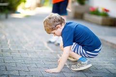 Peu garçon drôle blond d'enfant jouant le jeu de marelle sur le terrain de jeu dehors Images stock