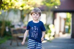 Peu garçon drôle blond d'enfant jouant le jeu de marelle sur le terrain de jeu dehors Photographie stock libre de droits