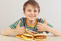 Peu garçon drôle dans une chemise rayée à la table recommande les hamburgers et le sandwich sur le fond blanc photographie stock