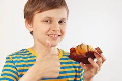 Peu garçon drôle dans une chemise rayée recommande le gâteau aux pommes doux sur le fond blanc image stock