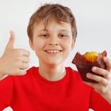 Peu garçon drôle dans une chemise rouge recommande le petit pain sur le fond blanc image libre de droits
