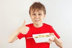 Peu garçon drôle dans une chemise rouge recommande les nouilles instantanées sur le fond blanc photos stock