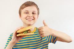 Peu garçon drôle recommande et aime le grand hamburger sur le fond blanc photos libres de droits