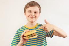 Peu garçon drôle recommande le grand hamburger sur le fond blanc photographie stock libre de droits