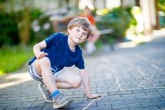 Peu garçon drôle blond d'enfant jouant le jeu de marelle sur le terrain de jeu dehors Photographie stock