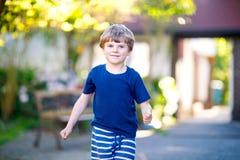 Peu garçon drôle blond d'enfant jouant le jeu de marelle sur le terrain de jeu dehors Image stock
