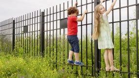 Peu garçon et fille s'élevant sur la barrière de fer dans la campagne Enfants espiègles ayant l'amusement dans le village aux vac banque de vidéos