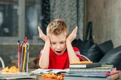 Peu garçon faisant des devoirs à l'école image libre de droits