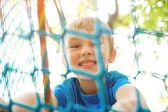 Peu gar?on jouant au parc d'aventure de corde Concept de vacances d'?t? Enfant mignon ayant l'amusement dans le tunnel net Parc d photos stock